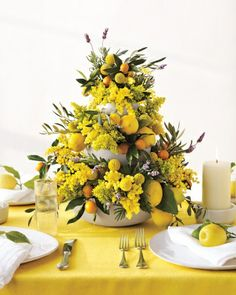Tiered bowls are filled with dense tufts of goldenrod, fuzzy clusters of mimosa, globelike craspedia balls, olive leaves, kumquats, lemons, and sprigs of fresh lavender