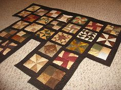 You have to use your imagination a little on this one.  Consider this as a partial quilt.  This is a sampler style with different block designs and nice dark borders in chocolate (we could do hunter green borders too) earthi quilt