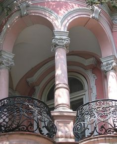 Pink balcony from what appears to be a Victorian home