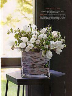 White tulips in bark lined glass vase