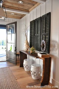 Front door!  Black  white with rustic elements.  Board  batten trim, organic console table, ceramic garden stools, light-toned wood flooring, sisal rug, rustic inset wood paneling in ceiling.