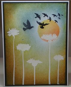 card with a flock of birds flying off...lovely sponging to create skey over & around white heat embossed flowers...