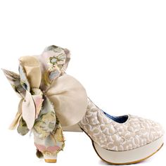 Stand out from the crowd in these extraordinary pumps from Irregular Choice. Sweety Bird has a 4 inch cream heel and a 1/2 inch platform. This style has cream fabric upper with a white pattern design.  A large gorgeous fabric flower adorns the back in floral and neutral prints.
