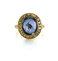 English, circa 1300 -  SIGNET RING - the gold inscribed in Lombardic script: Amor Vincit Omnia (love conquers all), the intaglio carved with an eagle bearing a laurel wreath in its beak gold, set with a Roman, 1st/ 2nd century AD, onyx agate nicolo intaglio