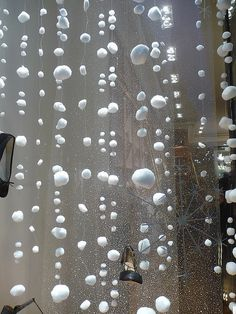 Thread cotton balls to make fake snow. This would look cute with the mini christmas bulbs hanging from the window mixed in.