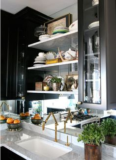 mirrored backsplash, black cabinets, brass faucet.