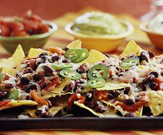 Balance the hot bean-and-cheese-topped chips with cool salsa, guacamole, and sour cream for a party appetizer that is always in demand.