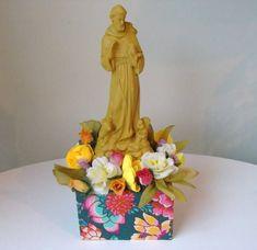 Imagem coloridas de santo com pedestal e flores