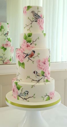 Hand painted wedding cake featuring illustrations of British garden birds. tall 4 tier cake in pink and sage green. Hand painted with cocoa butter paint. Design by Emily Hankins Cakes