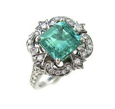 An emerald, diamond and eighteen karat blackened gold ring of antique design, centering an emerald-cut emerald, set in horizontal fashion, surrounded by round brilliant-cut diamond