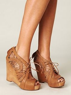 Gorgeous lace-up wedge with elaborate cut-out leather upper, peep toe opening, and zipper closure in the back. Wood platform. Cork lining