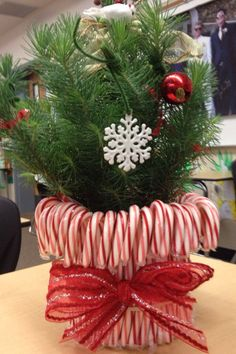 Candy Cane Vase Copied from other pinners. Put a rubber band around an old candle jar, put candy canes behind the rubber band, tied a ribbon around the band and put a Christmas plant inside. Made a great gift!