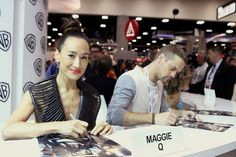NIKITA's Maggie Q and Shane West sign for fans at the Warner Bros. booth #CWSDCC #WBSDCC (©2013 WBEI. All Rights Reserved.)