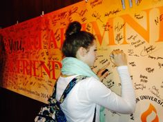 The Anderson University Student Alumni Association sponsored the 4th annual Tuition Freedom Day. Freshman Hannah Unis signs a banner saying thank you in celebration of the support AU receives from alumni and friends of the university.