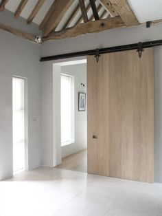 sliding contemporary barn door | old oak beams raw and pale | clean white crisp architecture || McLaren.Excell