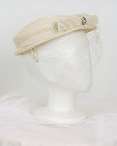 1950's ivory straw hat with veil (side view) | Wide flat top with ribbon trim and straw bow in front decorated with rhinestone brooch. Delicate veil in front and fabric prongs on the inside to keep it on the head