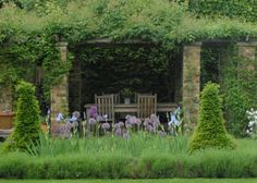 Dining area at Raworth: Pergola over the table and a border with evergreens, allium and irises.