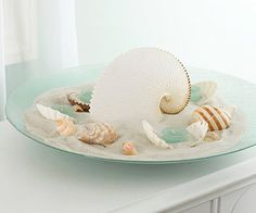 Beachside Comes Inside  How to Make It:   1. Start with a large, shallow glass bowl.   2. Create a center mound of sand, leaving a ring of glass showing, and place a large shell in the center. 3. Pour a small amount of sand into clamshells and nestle votive candles inside.   4. Arrange the clamshells around the large shell, and accent with smaller shells.