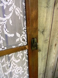 Old screen door with lace panels instead of screen. -