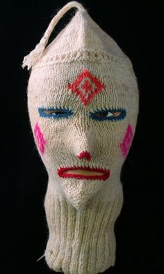 Knitted Mask. Bolivia. Dyed and natural wool. Bolivia has a rich masking traditions that includes many styles and methods of construction. Wool-knit masks with human features are used by the Kollas of Puno and Paucartambo, and other cloth masks are worn by the Kusillu of the Altiplano. Though this mask is inspired by that tradition, it was probably made for sale to tourists.