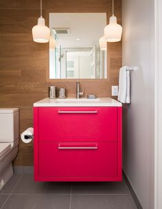 A hot pink bathroom vanity adds a fun punch of color to a natural, traditional bathroom
