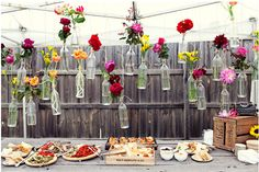 Flowers in wine bottles outside parties, flower centerpieces, hanging flowers, outdoor parties, garden parties, beer bottles, wine bottles, garden weddings, bottles hanging from trees