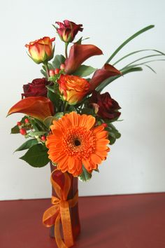 Rich Fall colors of Mango Mini Calla Lilies, Roses, Hypericum Berries, Orange Gerbera Daisy & Lily Grass, create a beautiful Fall arrangement!