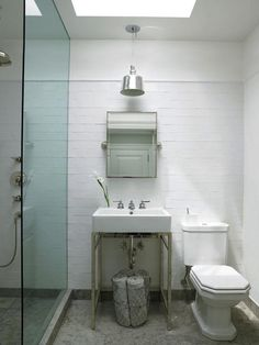 The clean and simple look of this industrial-accented bathroom. A glass shower without a door to help open up the small space and added a large skylight to bring in natural light.