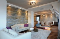 Modest living room design with wood floor, brick wall framed with white.  White color scheme continued with white sofas and off-white rug.