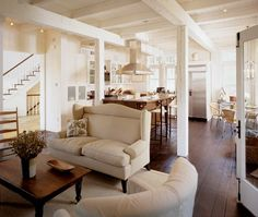I love this kitchen in so many ways: beams, sofa, rustic hardwood, hood range over center island