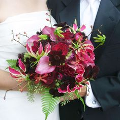 Reds, Purples & Dark Pink Explore the spectrum of reds for your winter wedding by decorating in shades of the hue ranging from bright pink to purple. In a bouquet, the colors pop against a simple white wedding gown. Here, we used chocolate cosmos, calla lilies, gloriosa lilies, dahlias, orchids, seeded eucalyptus, and ferns for this informally arranged bouquet.