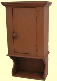 "This Waterbury Hanging Cupboard captures the true look and feel of Colonial America, recreating 17th, 18th, and 19th century primitive American country furniture.  It is an authentic design, handmade, then painted with an authentic milk paint color, and finished with a timeworn and aged patina, giving it that original old look.  Measures High x 21"" Wide x 11"" Deep"