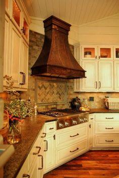 copper hood & brick like tile on white kitchen