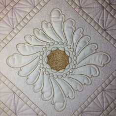 A Patsy Thompson feathered wreath stencil quilted with gold and silver Glide thread