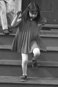 Girl wearing pleated dress on steps, 1967