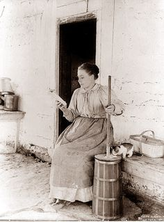 Reading while churning butter (with a cute kitten cleaning up any overflow), 1897. #Victorian #vintage #domestic_life