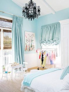 Light blue girls bedroom with black chandelier and ruffle curtains.
