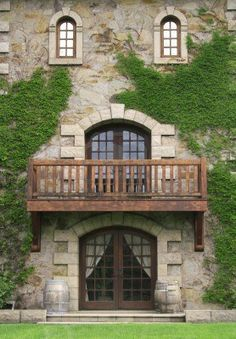 Architectural detail of a castle facade, entrance. Windows, balcony, front door, wall covered by ivy Stock Photo - 2813202