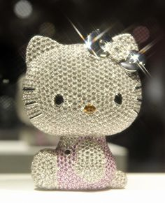 """Hello Kitty jewel doll. This 4-inch """"doll"""" is made of solid platinum studded with thousands of precious gems, including 1,939 pieces of white topaz, 403 pink sapphires, a pair of black spinels for her eyes, a citrine for her nose and a 1.027-carat diamond on her signature bow. The valued at 15 million yen—about US $167,000!"""