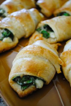 Cheesy Spinach Crescent Rolls  2 tubes crescent rolls, Pillsbury (8 ct. each) 4 oz. crumbled feta cheese 4 oz. shredded mozzarella cheese 3 oz. fresh baby spinach, chopped (about half of a pre-washed bag) 1 egg white, beaten 1/4 tsp. red pepper flakes dash of salt and pepper