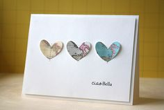 handmade card: The Map to Your Heart Challenge by L. Bassen ... clean and simple design ... three hearts cut from map paper ... set it a row ... each machine stitched to the card ... lu the elegant simplicity of this card ...