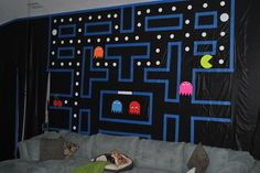 Possible photo booth backdrop: one roll of black plastic table cloth material, thick blue painter's tape for the lines, and card stock for the dots, ghosts and Pac-Man.