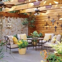 Garage Patio | This deluxe patio room used to be a rundown garage. To feel more intimate, the large, open space needed to be divided into rooms. Large containers of lush plants are grouped at varying heights to give this outdoor retreat scale. | SouthernLiving.com