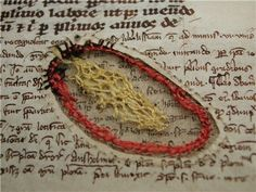 Medieval parchment —animal skin — that was stabbed, cut and stitched up. If the parchment maker pushed too hard while removing the unwanted parts like hair or fleshy bits, he would cut right through the surface. While some cuts were simply stitched up with a thin parchment cord, it also happened that book producers turned these defects into art.