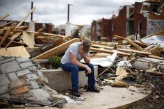 A man sits in front of a destroyed apartment building following the Joplin, Missouri tornado. (Reuters)