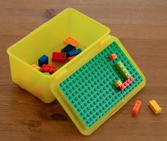 Use an old Baby Wipes container, hot glue or super glue a large Lego piece to the inside of the lid ...and you have a perfect Lego Travel Box