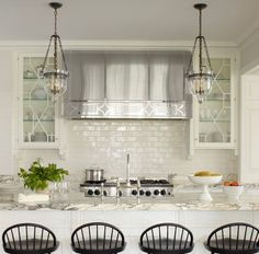 Gorgeous hood, white subway tile, thick marble counters, bell jar lanterns, cabinet front detail - Phoebe Howard