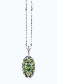 A BELLE EPOQUE DEMANTOID GARNET & DIAMOND PENDANT NECKLACE   The oblong-shaped pendant centering upon an oval-cut demantoid garnet, within a calibré-cut demantoid garnet surround, enhanced by rose-cut diamonds, suspended by a rose-cut diamond foliate bail, to the fine-link chain, spaced by rose-cut diamond navette-shaped links, joined by an old European-cut diamond clasp, mounted in platinum-topped gold, (chain not original to pendant), both ca 1900, 16 ins.  Clasp signed Tiffany & Co.