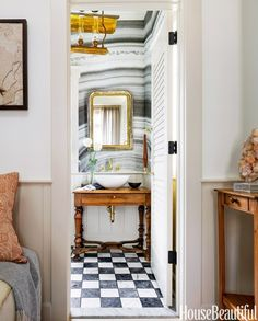 Marble wallpapered powder room with gilded mirror.