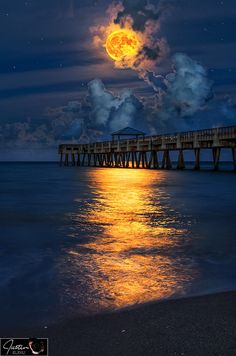 Full harvest moon over Juno beach pier by Justin Kelafus